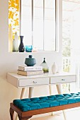 White-painted console table with drawers and bench with blue cushion below window