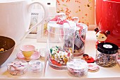 Sweets and sewing utensils in storage jars, Japanese doll, teacup and framed pictures on surface