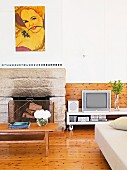 Sooty stone fireplace in pleasant, bright living room with wooden boards on wall and floor
