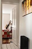 View from hallway with old radiator through open door to bedroom with handmade quilt
