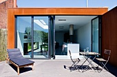 Terrace with lounger, table and chairs and a view through open folding doors into the kitchen