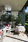 Conservatory with open, sliding glass wall, ornate metal furniture, luxuriant greenery and view of park