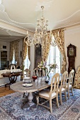 View from dining area with long dining table, fine silk rug and pretty chandelier hanging from stucco ceiling to living area with library