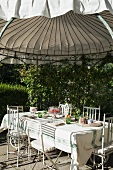 Set table and ornate metal chairs below round roof of climber-covered garden pavilion