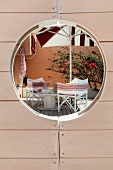 View through porthole in wooden door of wooden terrace with comfortable director's chairs and parasol