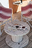 Upcycled table made from old cable reel on wooden terrace between two striped director's chairs