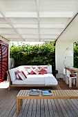 Veranda with comfortable lounger island in front of garden wall covered in lush vegetation