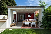 Outside living in summer: veranda with lounger combination, dining table and chairs
