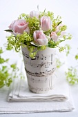Posy of roses and elderflower in vase wrapped in sheet music