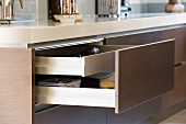 Open drawer with brown front integrated into kitchen island
