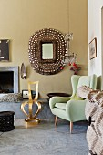 Lime green, retro wingback armchair and gilt chair in front of hand-crafted mirror on wall next to open fireplace