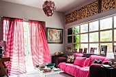 Comfortable sofa with pink scatter cushions and throw in front of lattice window; open terrace doors invite you to walk in the garden