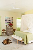 Bedroom in subdued shades with mosquito net above double bed with lime green throw; dog lying on cool stone floor