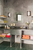 Elevation of concrete washstand with towel shelves below mirror and sconce lamps on concrete wall