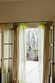 Opened French window with gauzy curtains leading to inviting exotic garden beyond