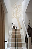 Tree silhouette painted on the wall at the top of a staircase with a runner made from antique linen grain sacks