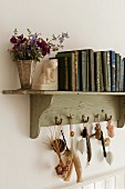 Vintage books on an old wooden bookshelf decorated with oddments found washed up on local beaches