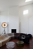 Modern sofa combo with color gradation in a living room with a high, pitched ceiling and dark wood floor
