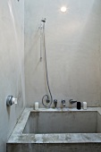 Minimalist shower stall made from raw concrete with stainless steel fittings