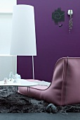 Contemporary designer couch next to white coffee table and minimalist standard lamp against purple wall