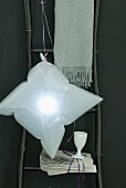 An inflated plastic bag functions as a home-made lampshade for an unusual pendant lamp