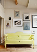 Yellow, vintage wooden bench against wall with gallery of contemporary art
