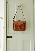 Vintage leather bag hanging from coat hook on white panelled door
