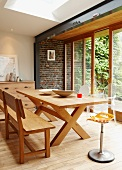 Contemporary, camping-style wooden table and bench in front of brick wall and large windows