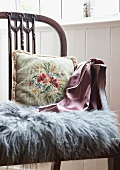 Floral embroidered cushion and grey fur mat on antique, English-style wooden chair