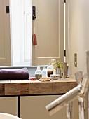Verschiedene Badutensilien auf rustikalem Waschtisch aus Holz vor halb geöffnetem Fensterladen