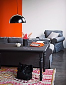 Wooden table lacquered with blackboard paint on a colorful, woven, ethnic carpet; behind a cozy gray armchair