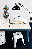 DIY, blue wooden table - table top decorated with adhesive paper with a sewing theme; on top a sewing machine a colorful mannequin