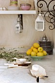 Mother-of-pearl dishes and a ceramic bowl of lemons on a tiled white worktop; lanterns hanging from ornate curved brackets which support the crockery shelf Eastern-style in a kitchen corner
