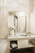 Schlichter Waschtisch aus heller Steinplatte mit eingelassenem Edelstahlbecken und beleuchtetem Spiegel in Wandnische eines orientalischen Bades