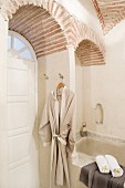 Dressing gown and towels in Oriental bathroom with vaulted brick ceiling and white, panelled arched door with fanlight