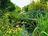 Leicht geschwungene Brücke, mit blauem Geländer und goldfarbenen Kreisen, über einen eingewachsenen Gartenteich in sommerlicher, idyllischer Stimmung