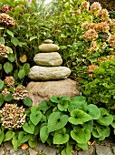 Beautifully placed stack of rough boulders getting smaller towards the top surrounded by hydrangeas and other garden plants in summer sunlight