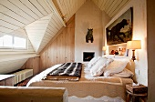 Cozy double bed and hunting trophies in an attic room - bedroom with pitched, wooden ceiling