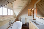 Small attic room - bathroom with vintage bath tub and simple wood and stone vanity