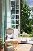 Rococo armchair in front of floor-to-ceiling, half-open terrace door with view of sunny terrace