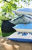 Stapel gemusterter Kissen in Blau-Weiss auf Terrassenplatten in Sommergarten