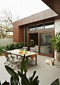 Refreshing drinks on terrace - dog next to table and chairs on tiled patio adjoining house with facade partially clad in rusty metal and open sliding door