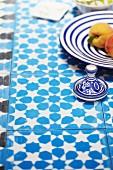 Blau-weiß geflieste Tischplatte mit floralem Muster und blau-weißem Geschirr