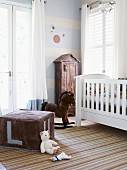 Nostalgic atmosphere in nursery with white cot, rocking horse and large, cubic, velour pouffe; small cupboard with roof against wall painted blue and white