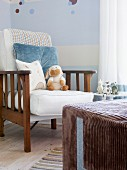 Armchair with cushions against wall painted pale blue and white and large, cubic pouffe with brown corduroy cover in corner of nursery with various soft toys decorating the pleasant room