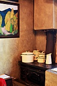 Battered enamel pots on old iron stove in corner of kitchen; framed picture on wall with antique-style marbled effect