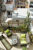 Airy roof terrace with comfortable wicker furniture, many potted plants, Indian parasol and view onto neighbouring terraces