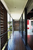 Wooden veranda with sliding wooden panels and metal railing