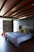 Bedroom with elegant wooden ceiling and sliding wooden panels in front of the wall of windows to provide sun protection; a large double bed in the middle