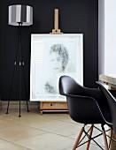 Antike Staffelei mit darauf stehendem, modernen Portrait vor schwarzer Wand; im Vordergrund schwarze Charles Eames Stühle